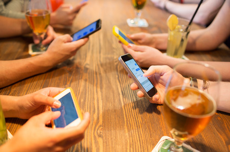 leisure, technology, lifestyle and people concept - close up of hands with smartphones messaging at restaurant