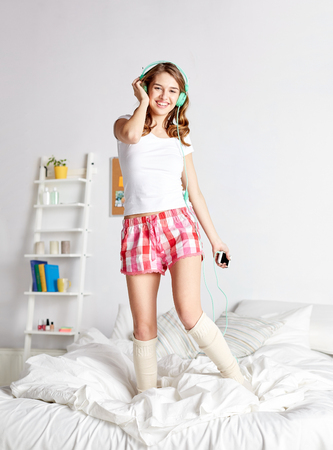 Photo pour people, leisure and technology concept - happy woman or teenage girl in headphones listening to music from smartphone and dancing on bed at home - image libre de droit