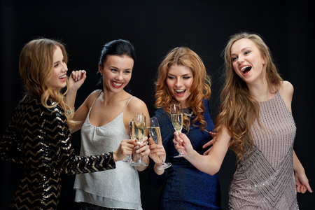 Foto de celebration, friends, bachelorette party and holidays concept - happy women clinking champagne glasses and dancing over black background - Imagen libre de derechos