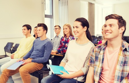 Photo for education, high school, teamwork and people concept - group of smiling students with notepads sitting in lecture hall - Royalty Free Image