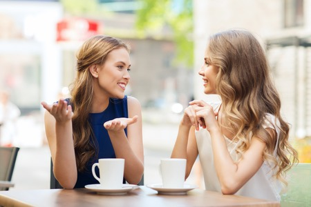 Photo pour people, communication and friendship concept - smiling young women drinking coffee or tea and talking at outdoor cafe - image libre de droit
