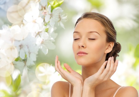 beauty, people, skincare, summer and health concept - young woman face and hands over green natural background with cherry blossom
