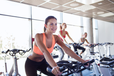 Photo for sport, fitness, lifestyle, equipment and people concept - group of women riding on exercise bike in gym - Royalty Free Image
