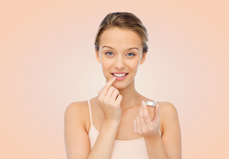 Foto de beauty, people and lip care concept - smiling young woman applying lip balm to her lips over beige background - Imagen libre de derechos