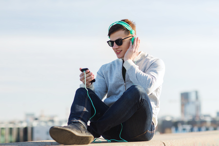 Photo for technology, lifestyle and people concept - smiling young man or teenage boy in headphones with smartphone listening to music outdoors - Royalty Free Image
