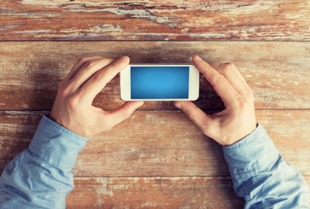 Photo pour business, education, people and technology concept - close up of male hands holding smartphone on table - image libre de droit