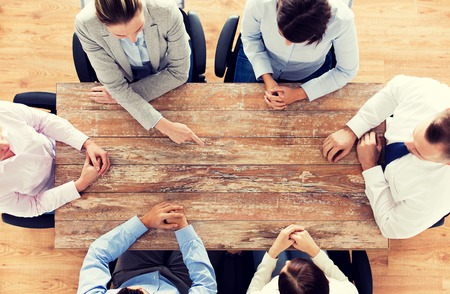 Foto de business, people and team work concept - close up of creative team sitting at table and pointing finger to something in office - Imagen libre de derechos