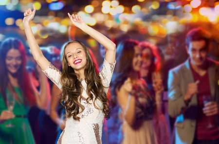 Photo for people, party, holidays, night life and entertainment concept - happy young woman or teen girl in fancy dress with sequins and long wavy hair dancing at disco club over crowd lights background - Royalty Free Image
