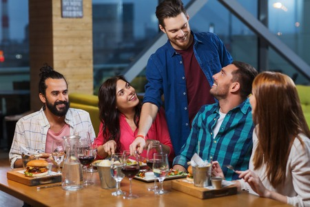 Photo pour leisure, eating, food and drinks, people and holidays concept - smiling friends having dinner and drinking red wine at restaurant - image libre de droit