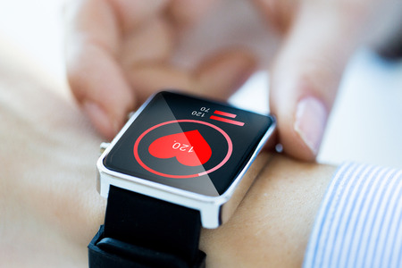 Photo pour technology, health care and people concept - close up of woman hands checking pulse by smartwatch with heart icon on screen - image libre de droit