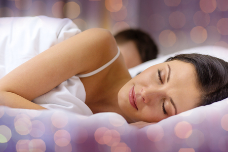 people, rest, relationships and holidays concept - happy couple sleeping in bed over lights background