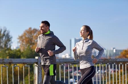 Foto de fitness, sport, people and lifestyle concept - happy couple running outdoors - Imagen libre de derechos