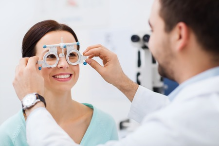 Photo pour health care, medicine, people, eyesight and technology concept - optometrist with trial frame checking patient vision at eye clinic or optics store - image libre de droit