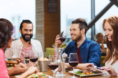Photo for leisure, eating, food and drinks, people and holidays concept - smiling friends having dinner and drinking red wine at restaurant - Royalty Free Image