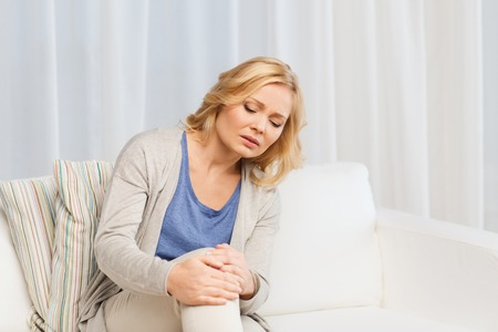 people, healthcare and problem concept - unhappy woman suffering from pain in leg at home