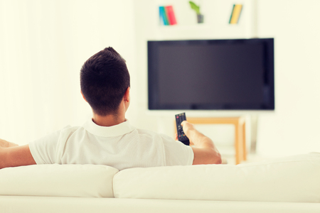 leisure, technology, mass media and people concept - man watching tv and changing channels at home from back