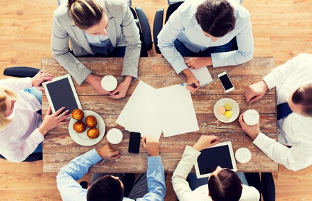 Foto per business, people, break and team work concept - close up of creative team meeting and drinking coffee with muffins during lunch in office - Immagine Royalty Free