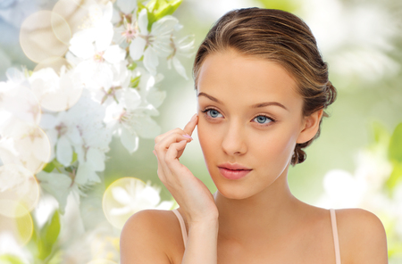 Foto de beauty, people, cosmetics, skincare and health concept - young woman applying cream to her face over green natural background with cherry blossom - Imagen libre de derechos