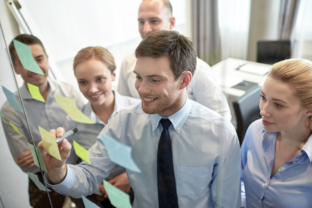 Foto per business, people, teamwork and planning concept - smiling business team with marker and stickers working in office - Immagine Royalty Free
