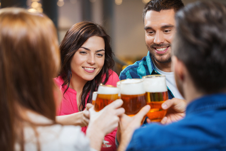 Photo pour leisure, drinks, celebration, people and holidays concept - smiling friends drinking beer and clinking glasses at restaurant or pub - image libre de droit