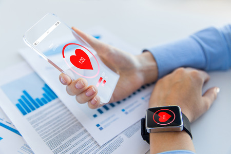 Foto de technology, health care and people concept - close up of woman hand holding transparent smartphone and smartwatch with heart icon at office - Imagen libre de derechos