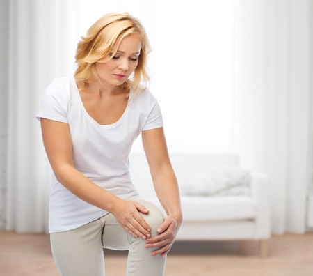 people, healthcare and problem concept - unhappy woman suffering from pain in leg over living room background