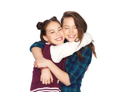Foto de people, friends, teens and friendship concept - happy smiling pretty teenage girls hugging - Imagen libre de derechos