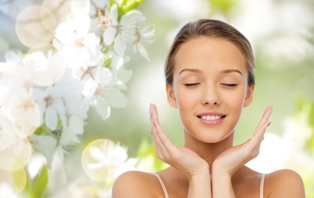 Foto de beauty, people, skincare and health concept - smiling young woman face and hands over green natural background with cherry blossom - Imagen libre de derechos