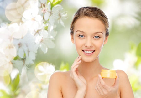 Photo pour beauty, people, cosmetics, skincare and cosmetics concept - happy young woman applying cream to her face over green natural background with cherry blossom - image libre de droit