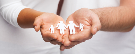 Photo for love and relationships concept - closeup of couple cupped hands showing paper man family - Royalty Free Image