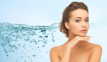 Photo pour beauty, people, moisturizing and health concept - smiling young woman with bare shoulders touching her face over water splash on blue background - image libre de droit