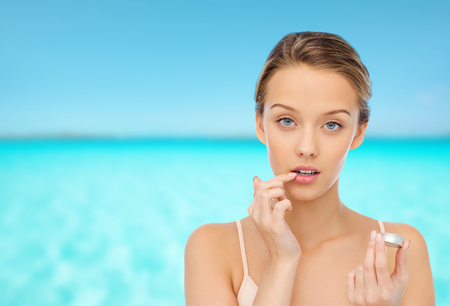 Photo pour beauty, people and lip care concept - young woman applying lip balm to her lips over blue sea and sky background - image libre de droit