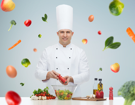 profession, vegetarian, food and people concept - happy male chef cooking and seasoning vegetable salad over gray background