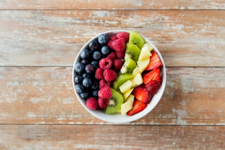 healthy eating, dieting, vegetarian food and people concept - close up of fruits and berries in bowl on wooden table