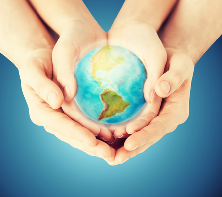 people, geography, population and peace concept - close up of woman and man hands with earth globe showing american continent over blue background