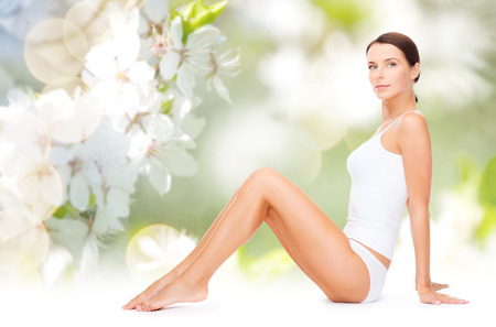 Photo pour people, beauty and body care concept - beautiful woman in cotton underwear showing her legs over green natural cherry blossom background - image libre de droit