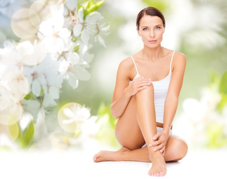 Photo for people, beauty and body care concept - beautiful woman in cotton underwear touching legs over green natural cherry blossom background - Royalty Free Image