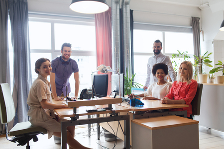 business, startup and people concept - happy creative team in office