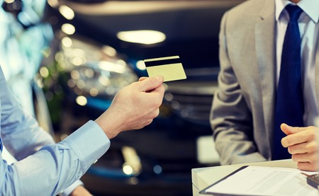 Foto de auto business, sale and people concept - close up of customer giving credit card to car dealer in auto show or salon - Imagen libre de derechos