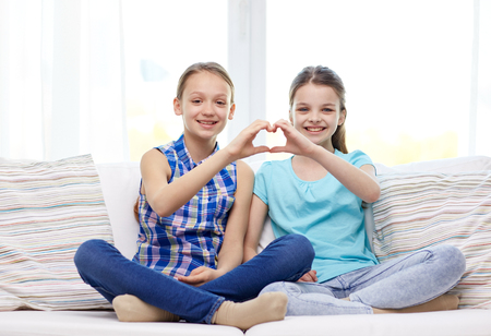 Photo pour people, children, friends and friendship concept - happy little girls sitting on sofa and showing heart shape hand sign at home - image libre de droit