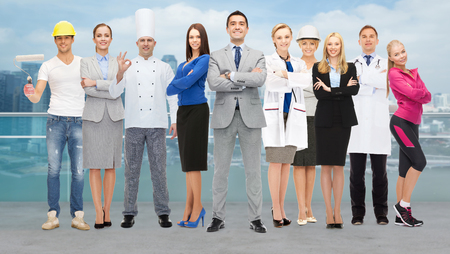 Photo pour people, profession, qualification, employment and success concept - happy businessman with group of professional workers over city background - image libre de droit