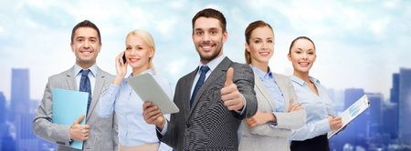 Foto de business, people, technology, gesture and office concept - group of smiling businessmen with tablet pc computer showing thumbs up over city background - Imagen libre de derechos