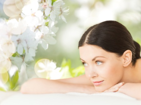 Photo pour people, beauty, spa and body care concept - happy beautiful woman lying on massage desk over green natural cherry blossom background - image libre de droit