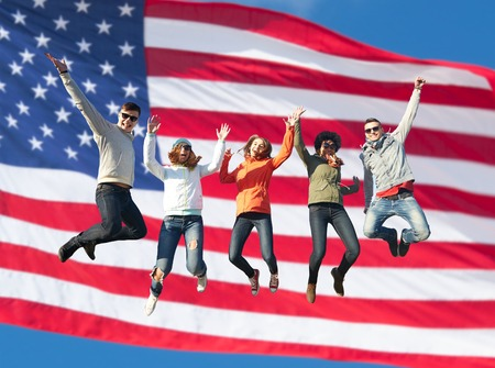 Photo pour people, freedom, happiness and teenage concept - group of happy international friends in sunglasses jumping high over american flag background - image libre de droit