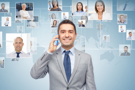 Foto de global business, people, network, communications and technology concept - happy businessman calling on smartphone over blue background with world map and contacts icons - Imagen libre de derechos