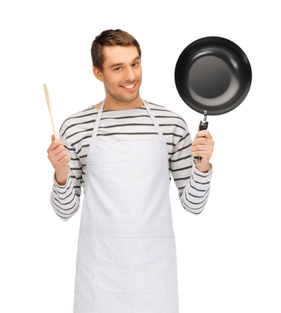 people, cooking and culinary concept - happy man or cook in apron with frying pan and wooden spoon