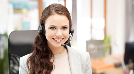 Foto de people, online service, communication and technology concept - smiling female helpline operator with headset over office background - Imagen libre de derechos