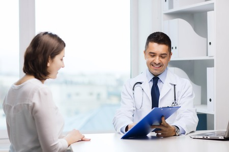 Photo pour medicine, health care and people concept - smiling doctor with clipboard and young woman meeting at hospital - image libre de droit