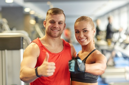 Photo pour sport, fitness, lifestyle, gesture and people concept - smiling man and woman showing thumbs up in gym - image libre de droit