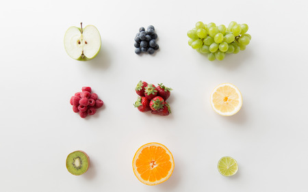 Photo pour diet, eco food, healthy eating and objects concept - ripe fruits and berries on white surface - image libre de droit